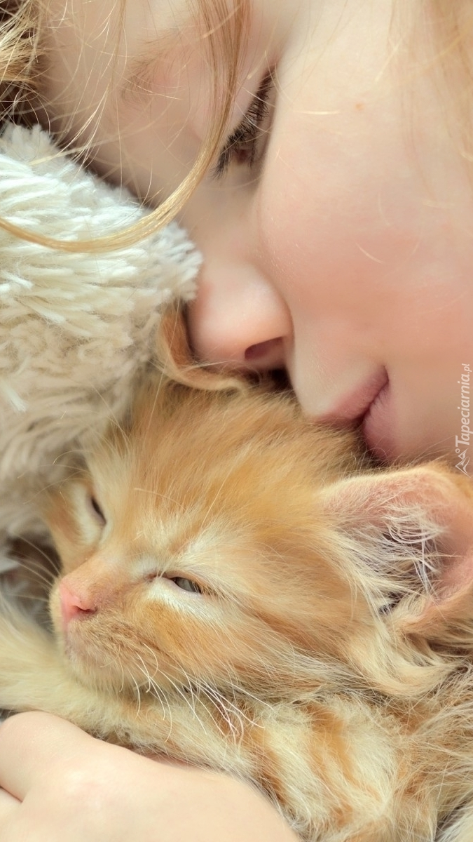 Dziecko przytulone do kotka