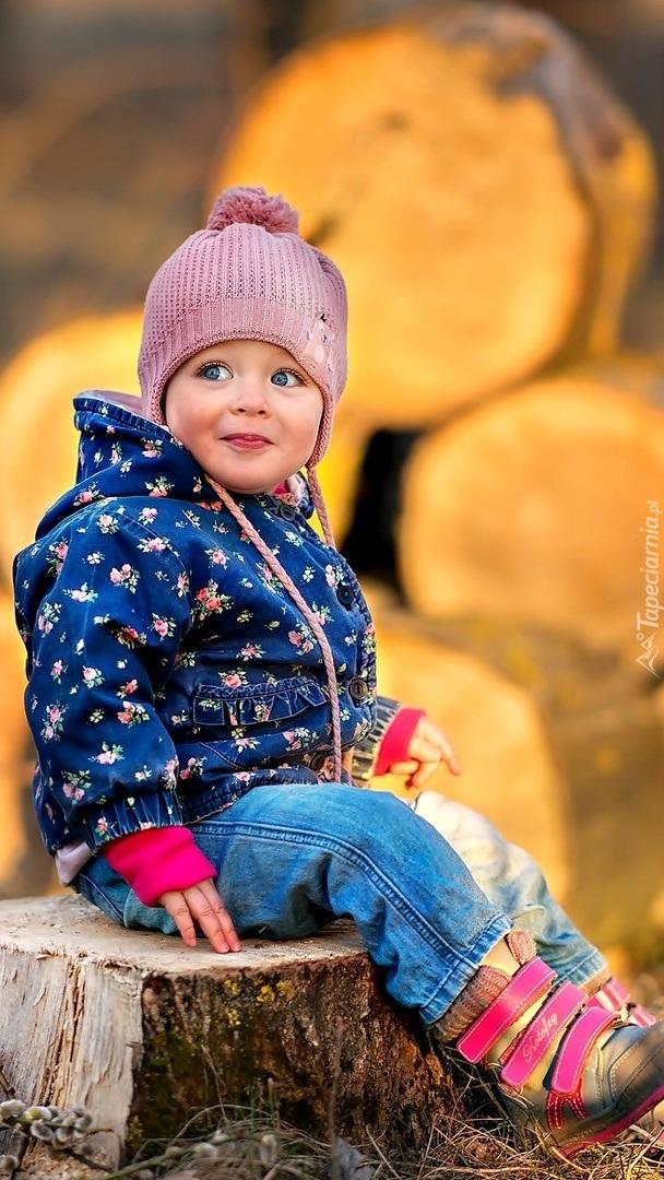 Dziecko w czapce na pniu