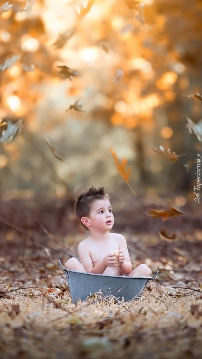 Dziecko w metalowej balii i jesienne liście