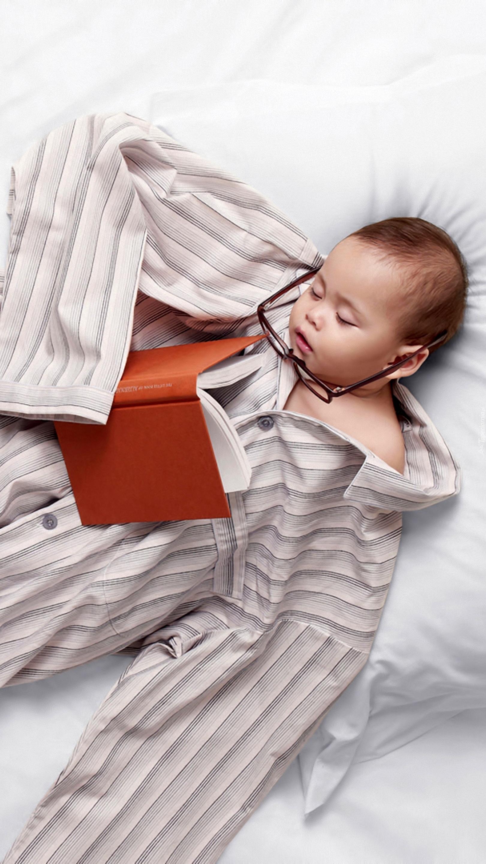 Dziecko w piżamie taty z okularami i książką