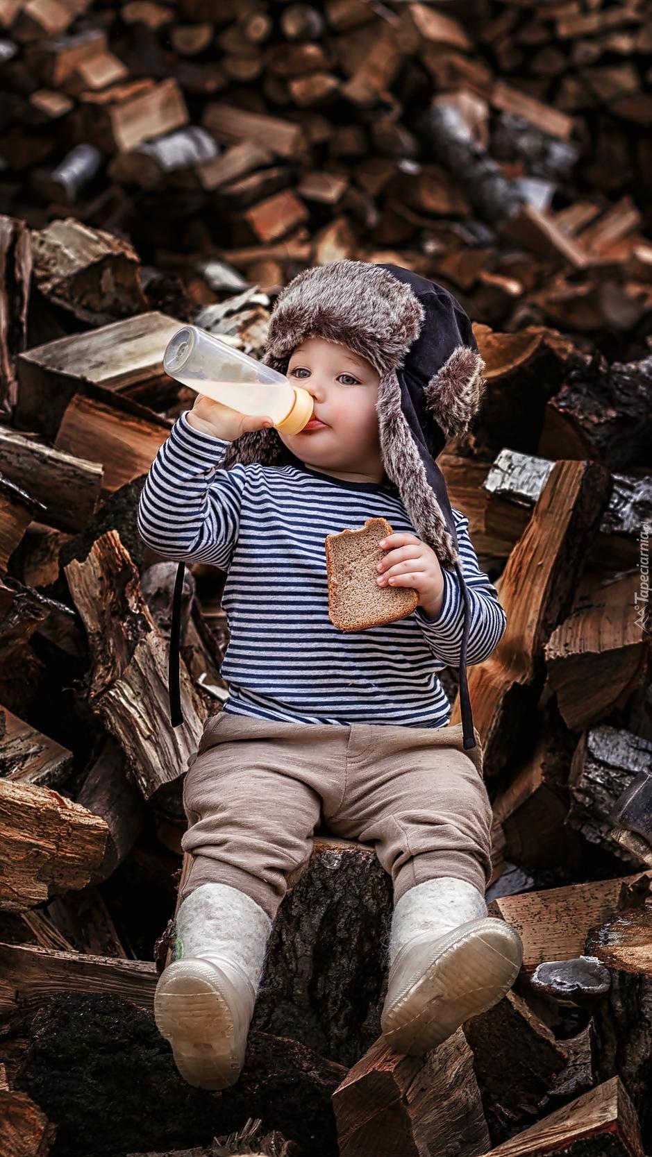 Dziecko z butelką mleka i chlebem