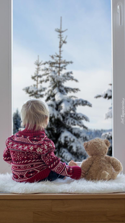 Dziecko z misiem przy oknie