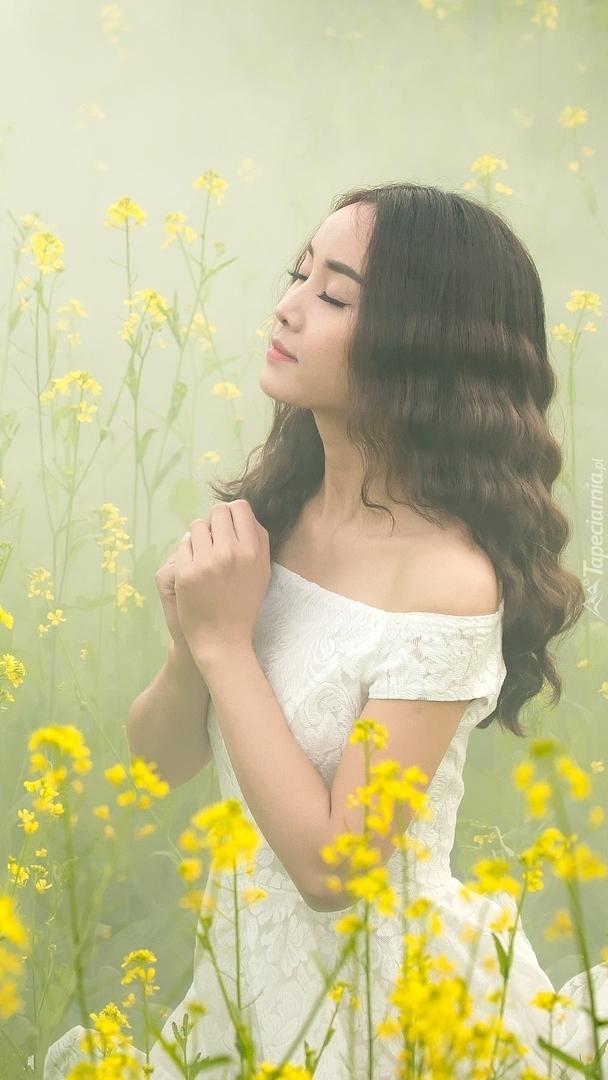Dziewczyna w białej sukience na zamglonej łące