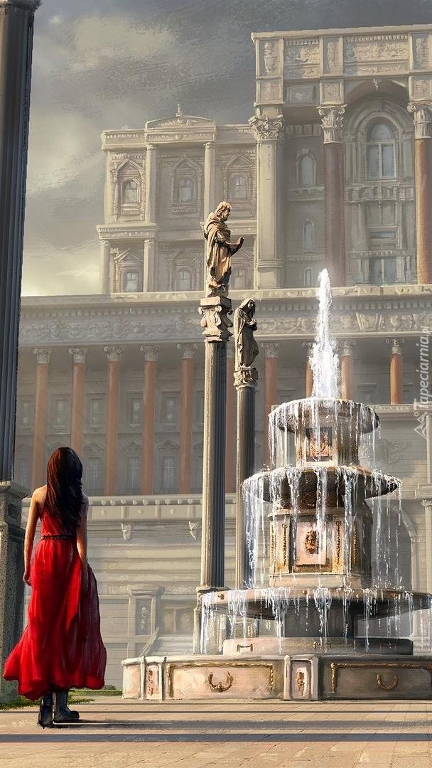 Dziewczyna w czerwonej sukience przed fontanną