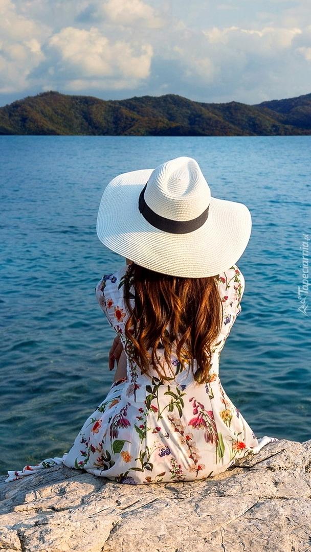 Dziewczyna w kapeluszu nad jeziorem