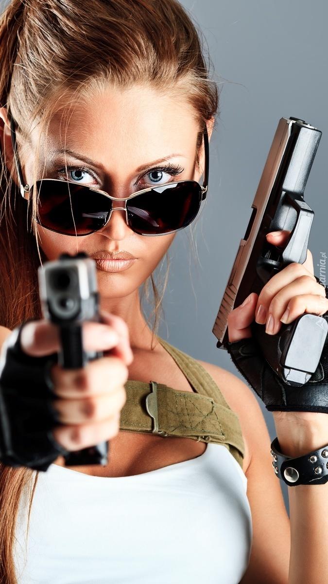Dziewczyna w okularach z bronią w rękach