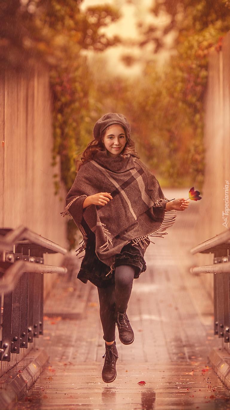 Dziewczyna w szalu biegnąca przez most