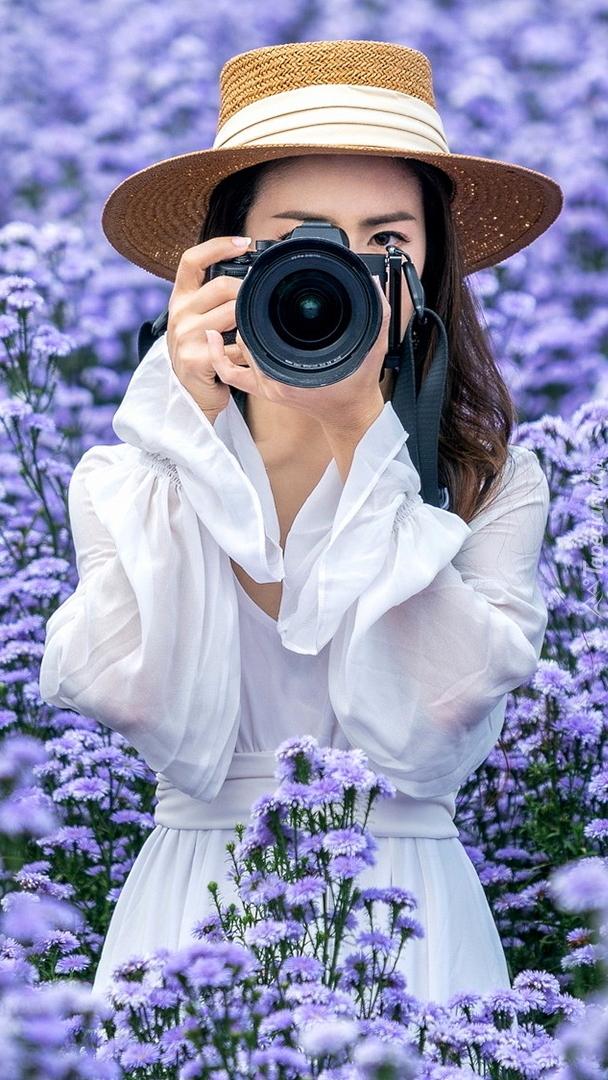 Dziewczyna z aparatem fotograficznym wśród kwiatów