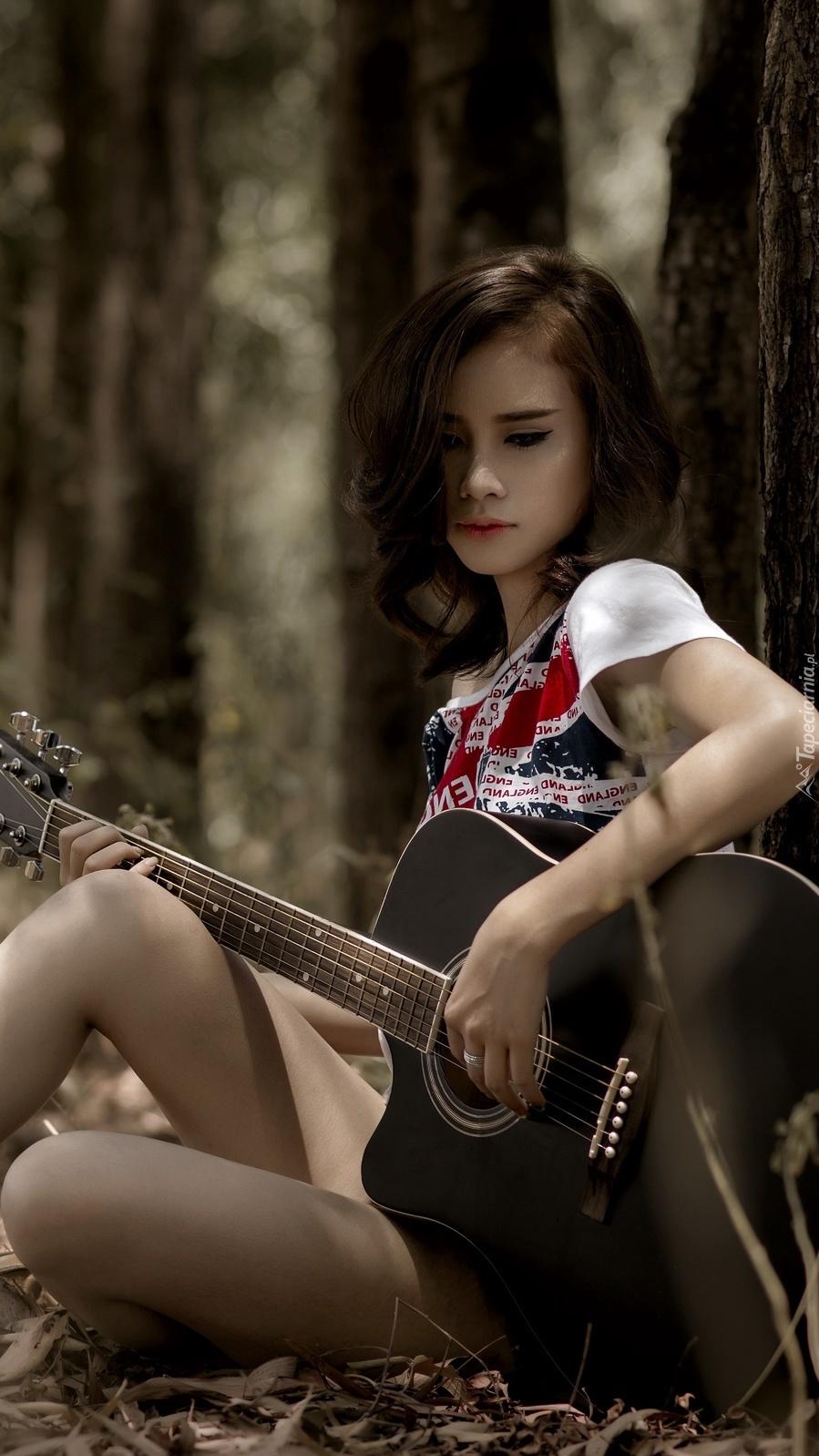 Dziewczyna z gitarą siedzi pod drzewem w lesie