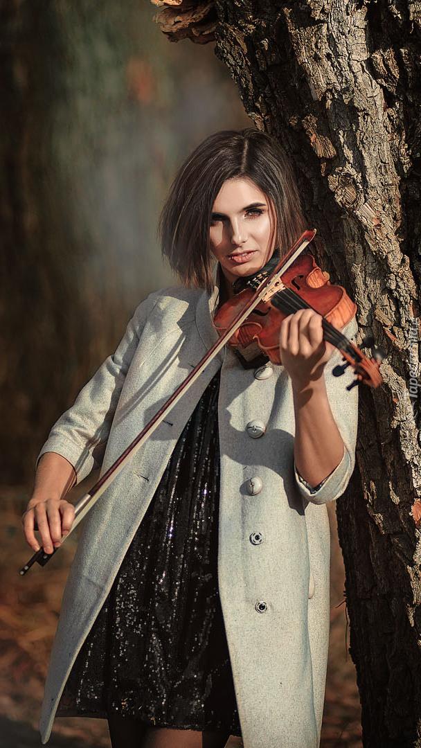 Dziewczyna ze skrzypcami pod drzewem