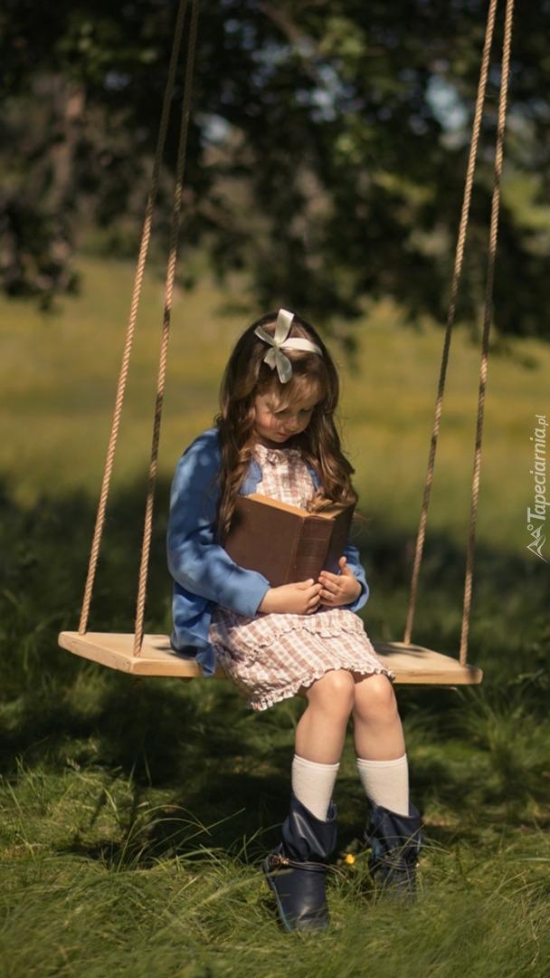Dziewczynka czytająca książkę na huśtawce