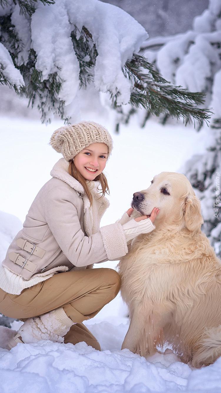 Dziewczynka i golden retriever po ośnieżonymi gałązkami