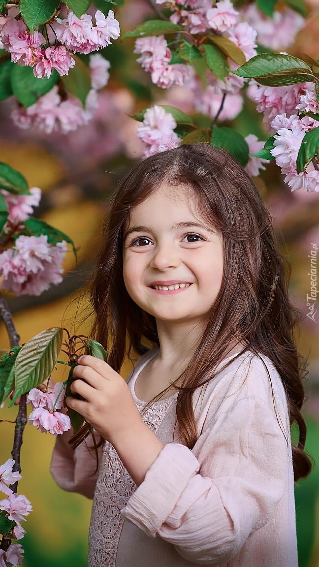 Dziewczynka pod kwitnącym drzewem