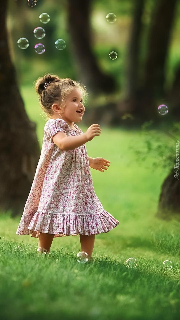 Dziewczynka pośród baniek mydlanych