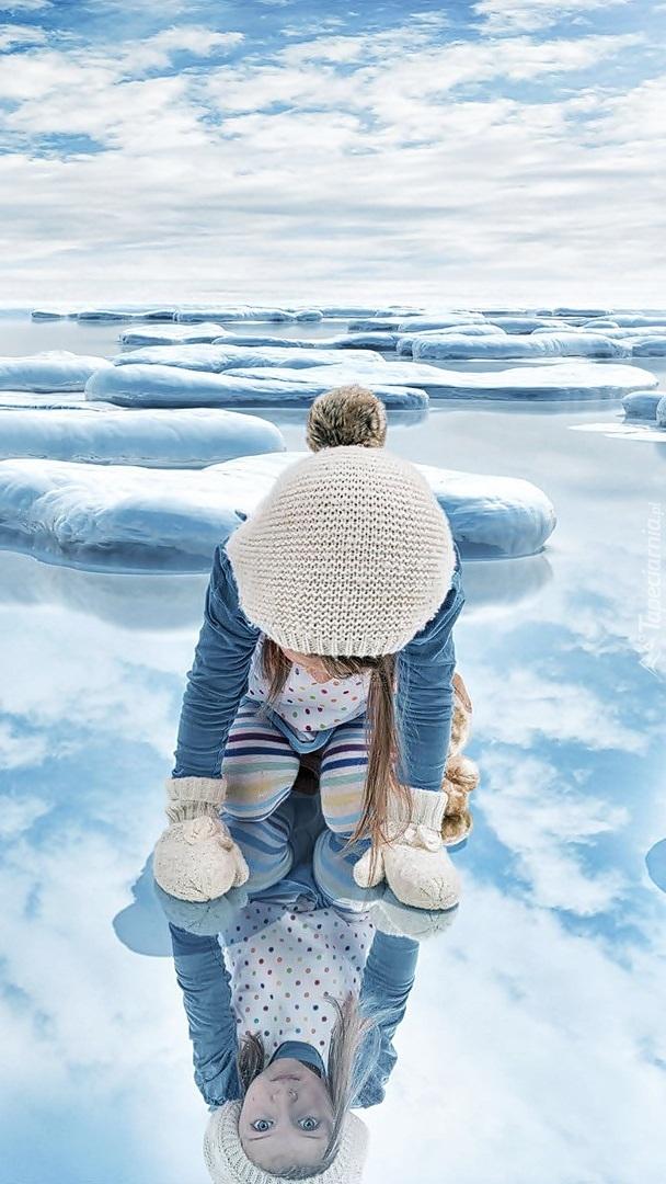 Dziewczynka przeglądająca się w tafli lodu