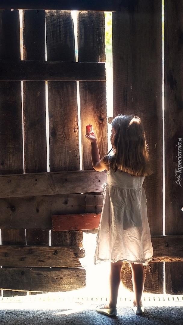 Dziewczynka przy drewnianych wrotach