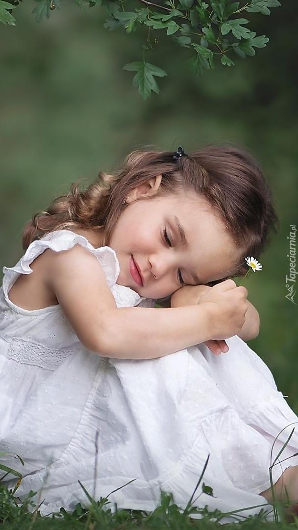 Dziewczynka w białej sukience na trawie