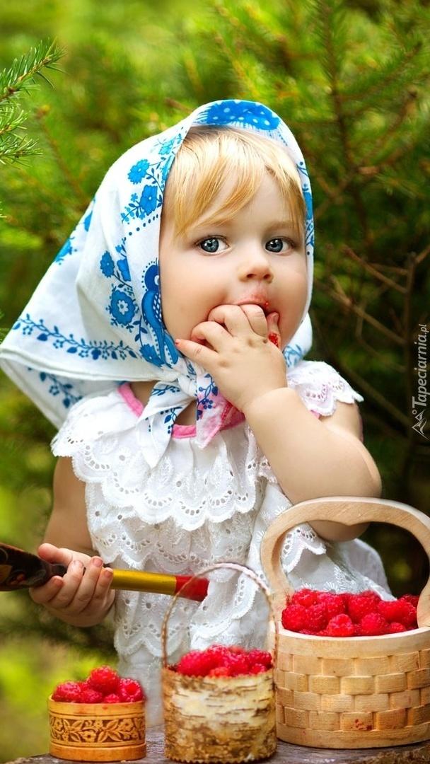 Dziewczynka w chuście zajadająca maliny z koszyczka