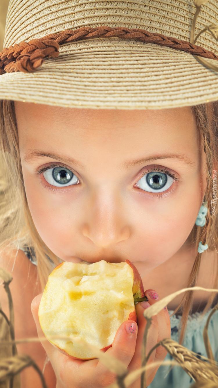 Dziewczynka w kapeluszu z jabłkiem
