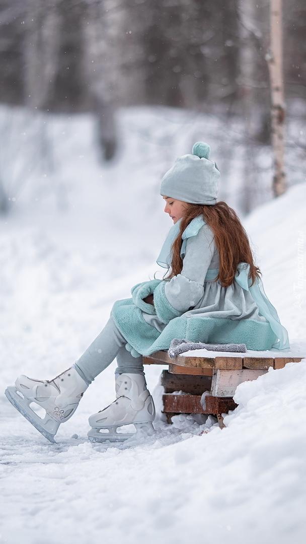 Dziewczynka w łyżwach siedząca na ławce