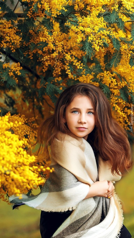 Dziewczynka w szalu pod kwitnącą akacją