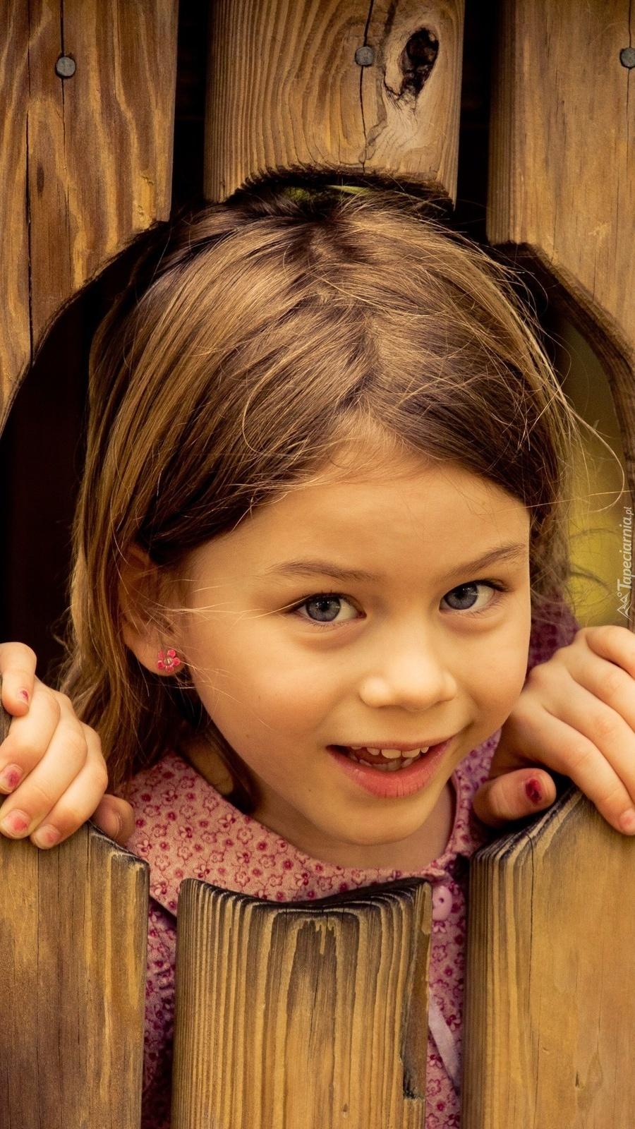 Dziewczynka wyglądająca przez dziurę w płocie