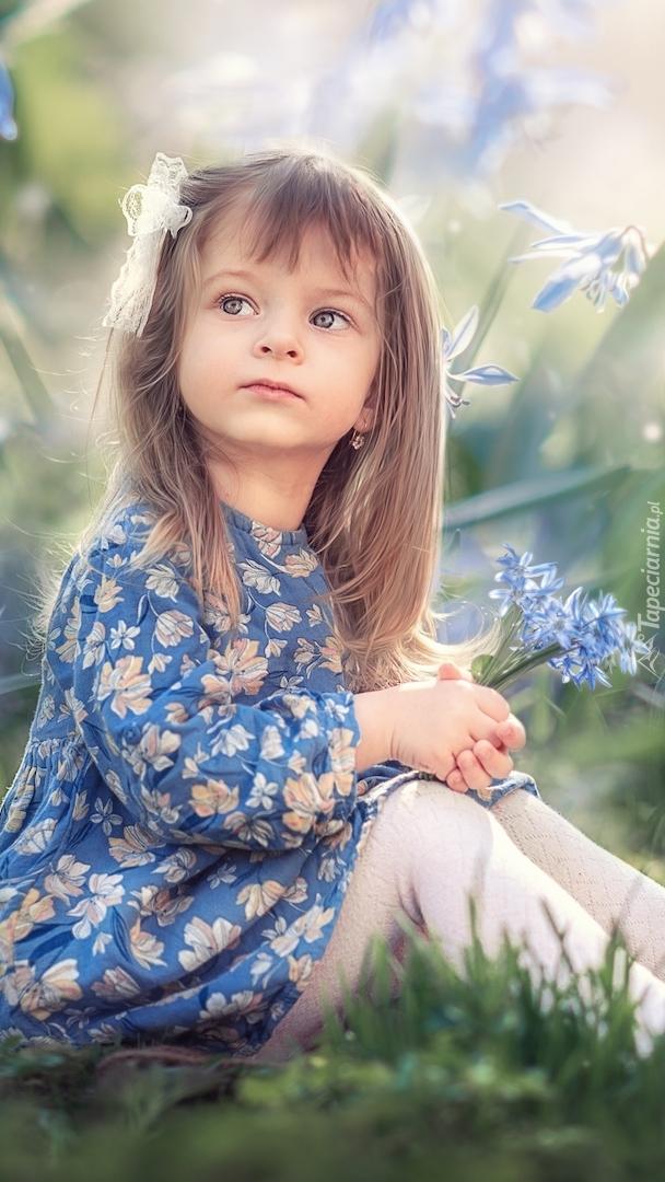 Dziewczynka z cebulicą syberyjską w rękach