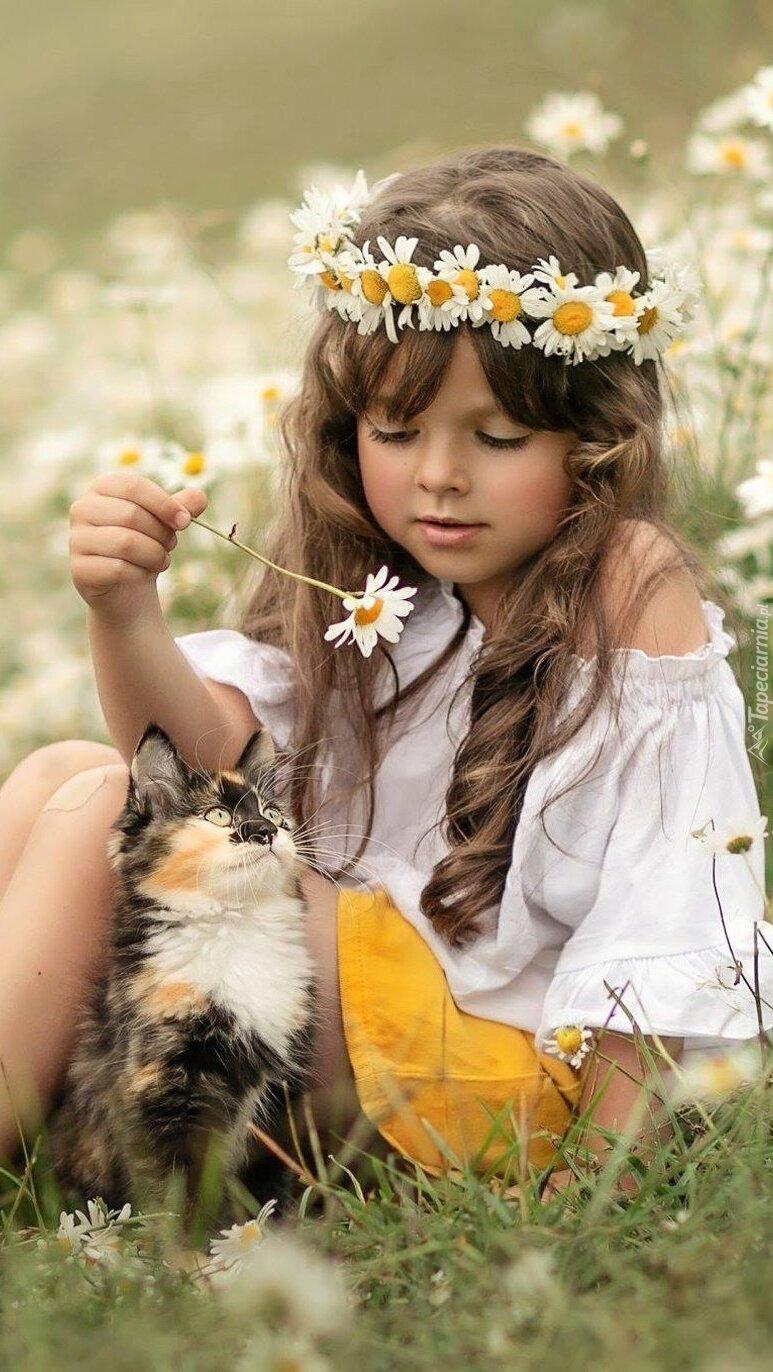 Dziewczynka z kotkiem na trawie