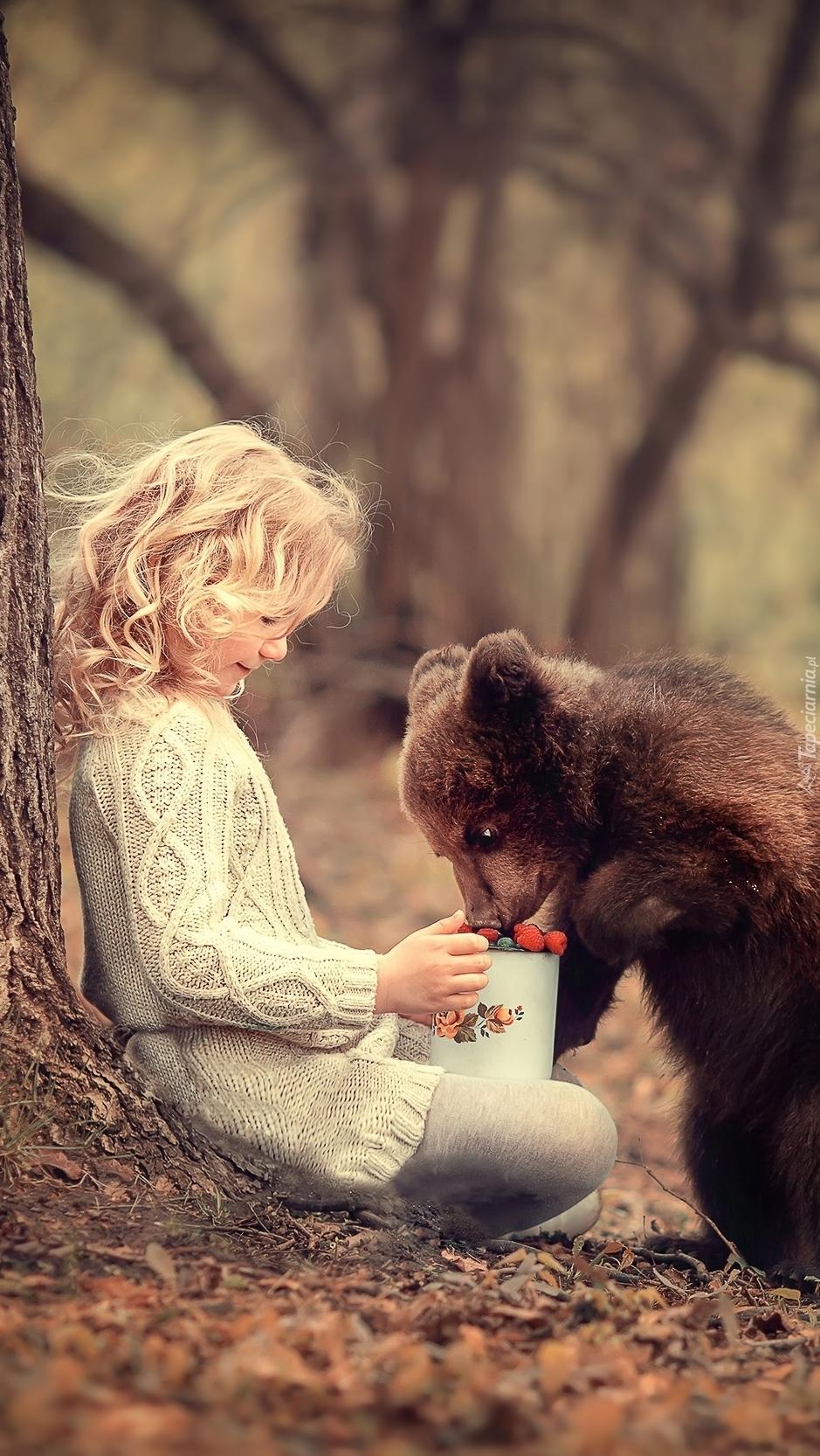 Dziewczynka z niedźwiadkiem pałaszującym leśne owoce