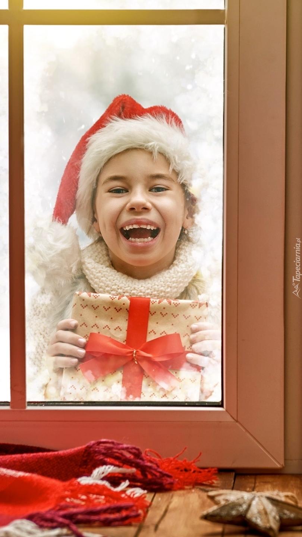 Dziewczynka z prezentem w oknie