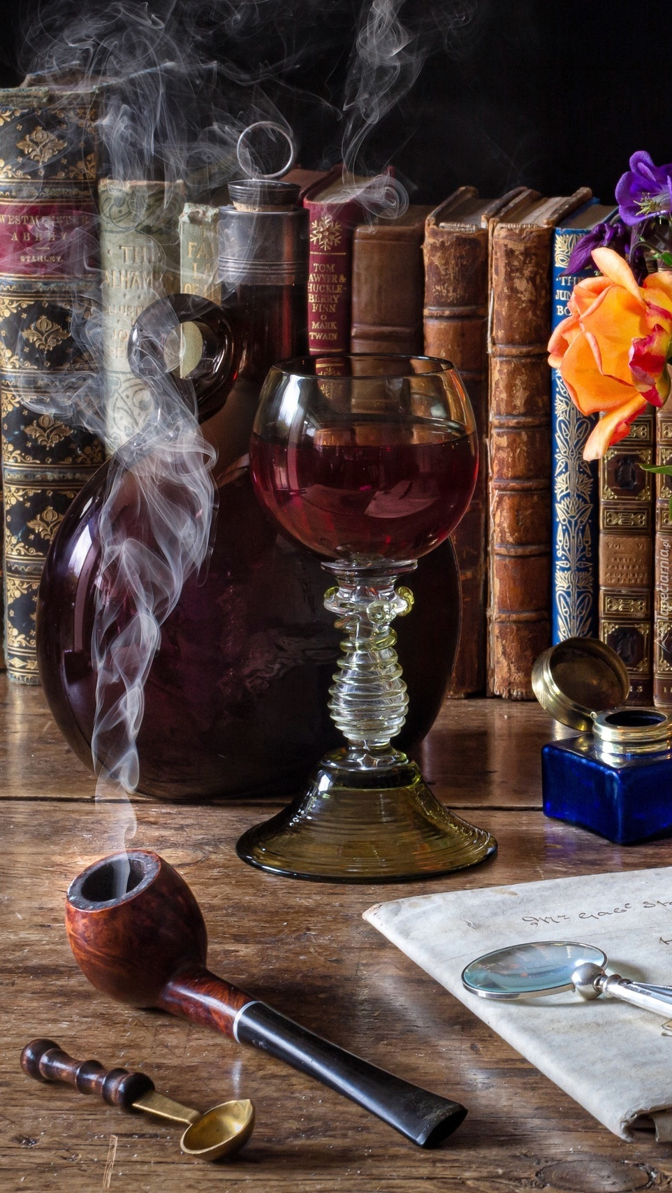 Fajka i kieliszek wina obok książek