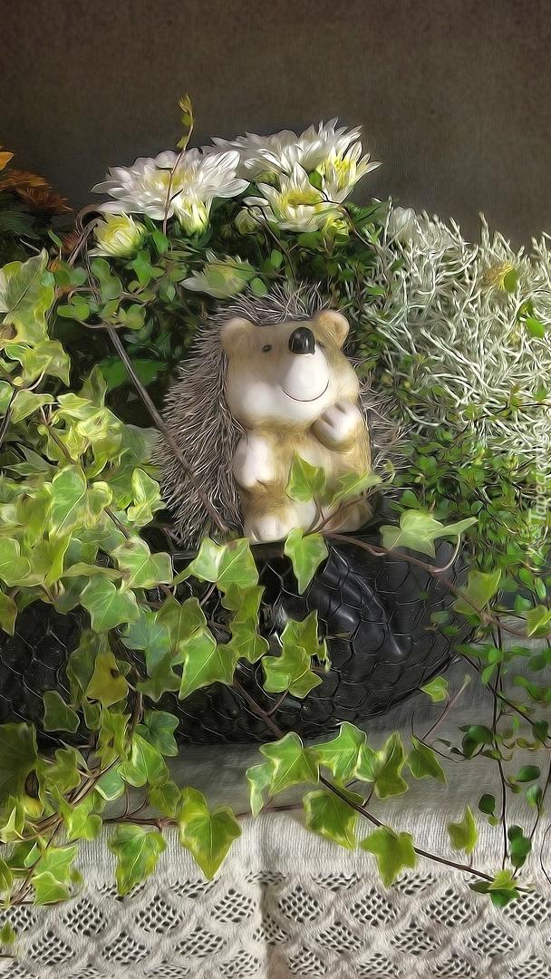 Figurka jeża w koszyku z roślinami
