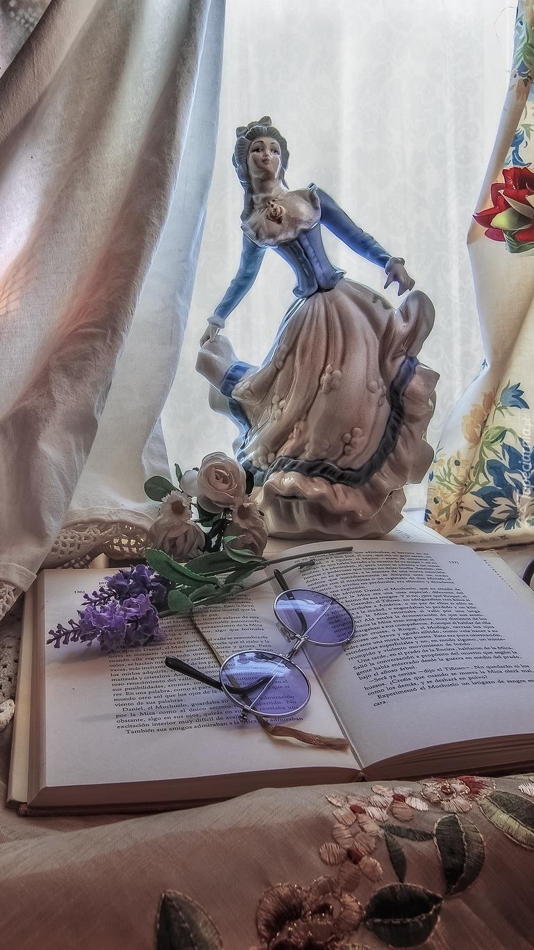 Figurka kobiety obok otwartej książki