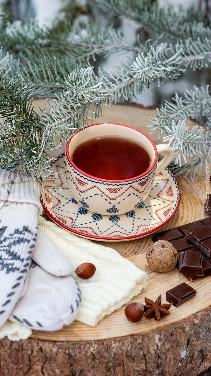 Filiżanka herbaty obok świerkowych gałązek