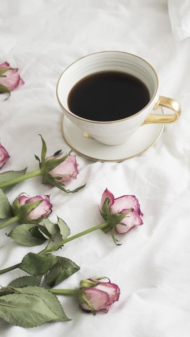 Filiżanka kawy obok róż