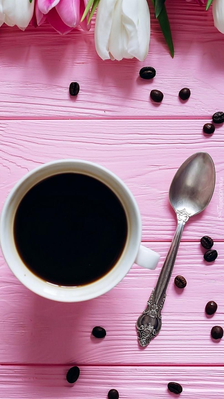 Filiżanka kawy z łyżeczką na różowych deskach