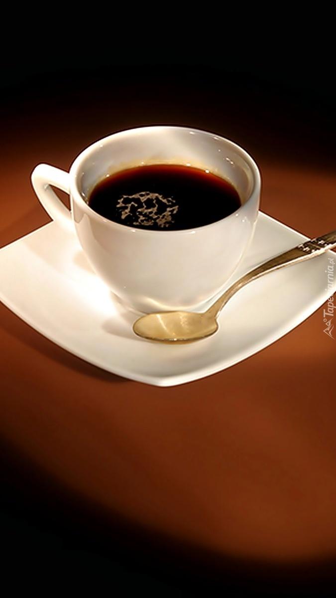 Filiżanka z kawą na spodku z łyżeczką