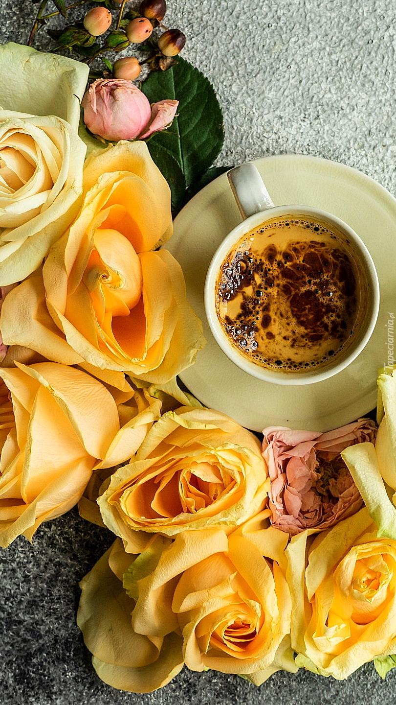 Filiżanka z kawą obok żółtych róż