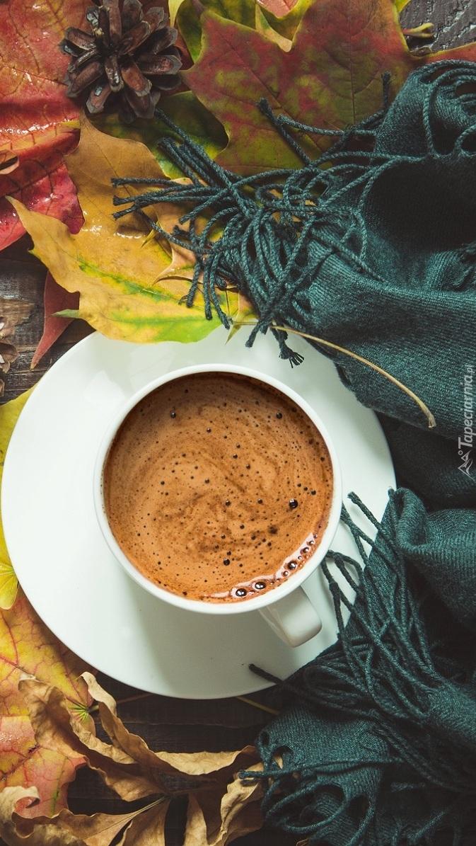 Filiżanka z kawą pośród jesiennych liści