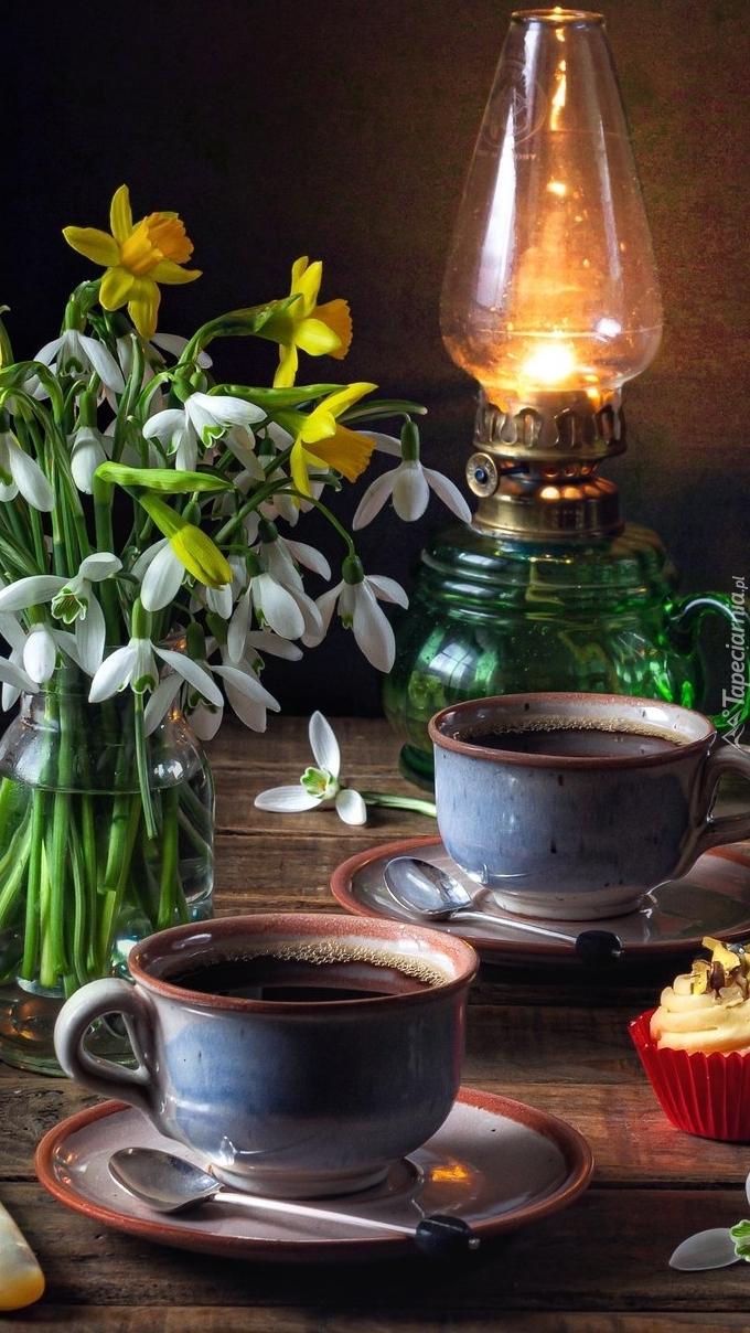 Filiżanki kawy obok lampy naftowej i przebiśniegów