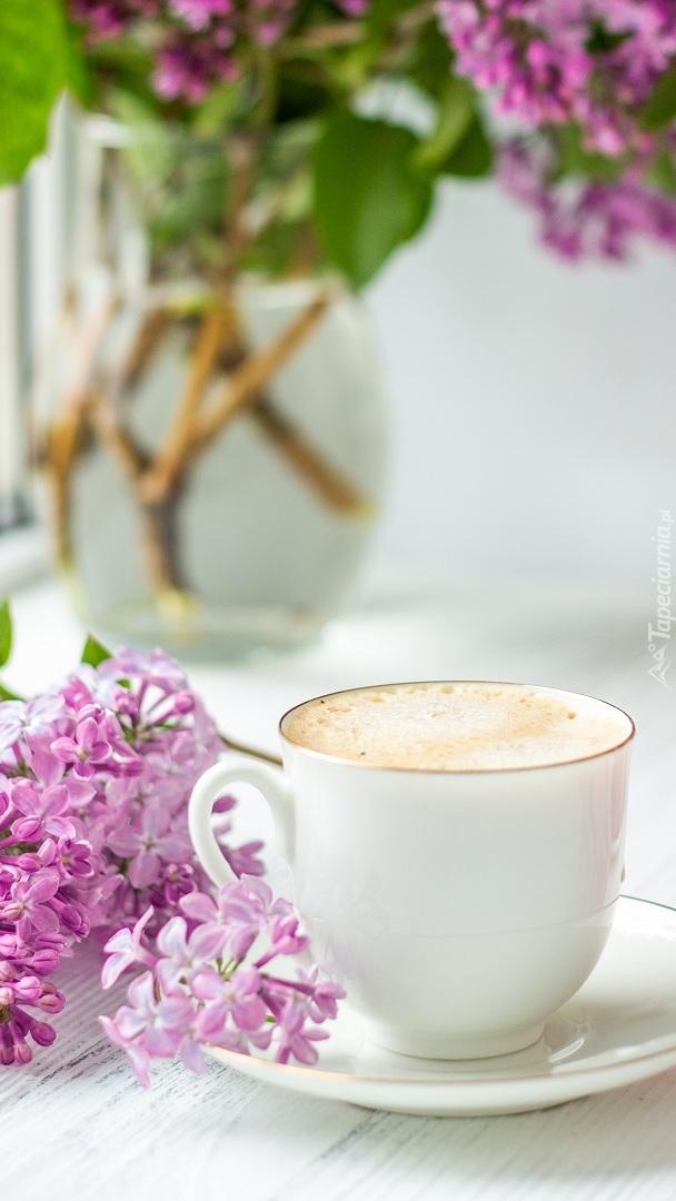 Gałązka bzu obok filiżanki z kawą