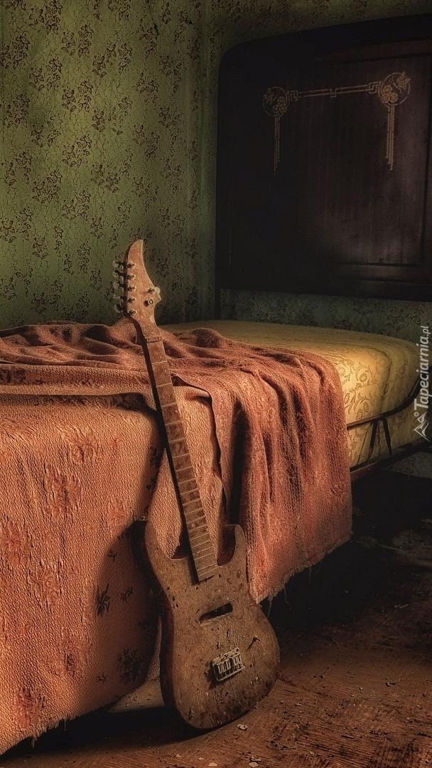 Gitara oparta o łóżko
