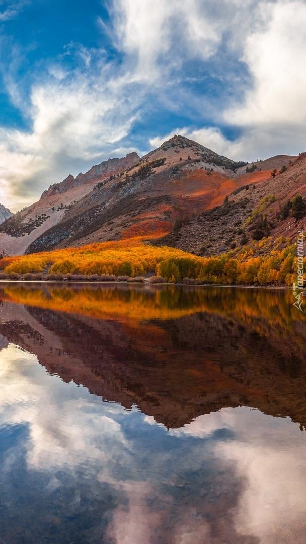 Góry i jesienne drzewa nad jeziorem