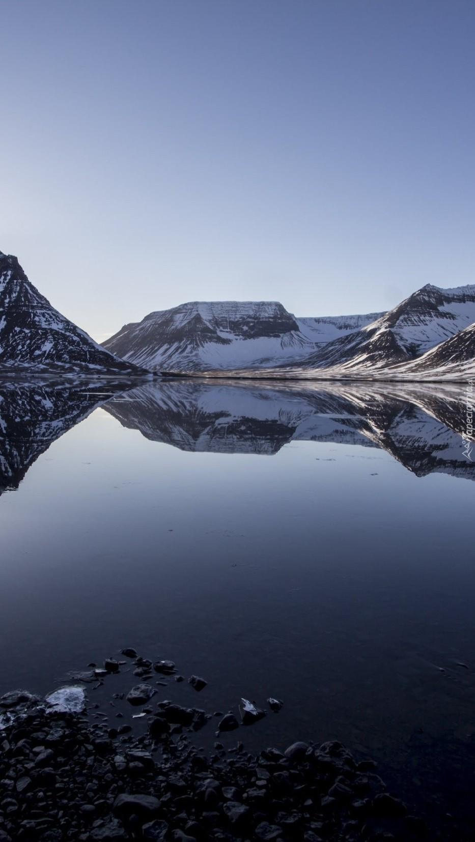 Góry w śniegu odbite w wodzie