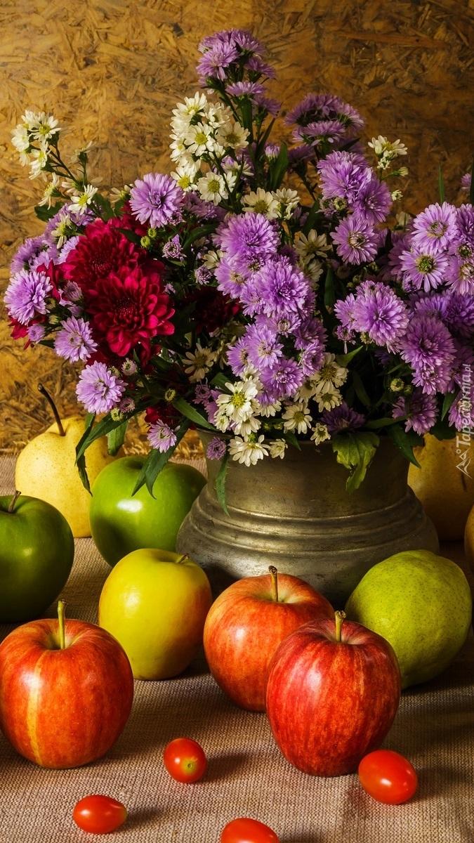Jabłka obok wazonu z astrami