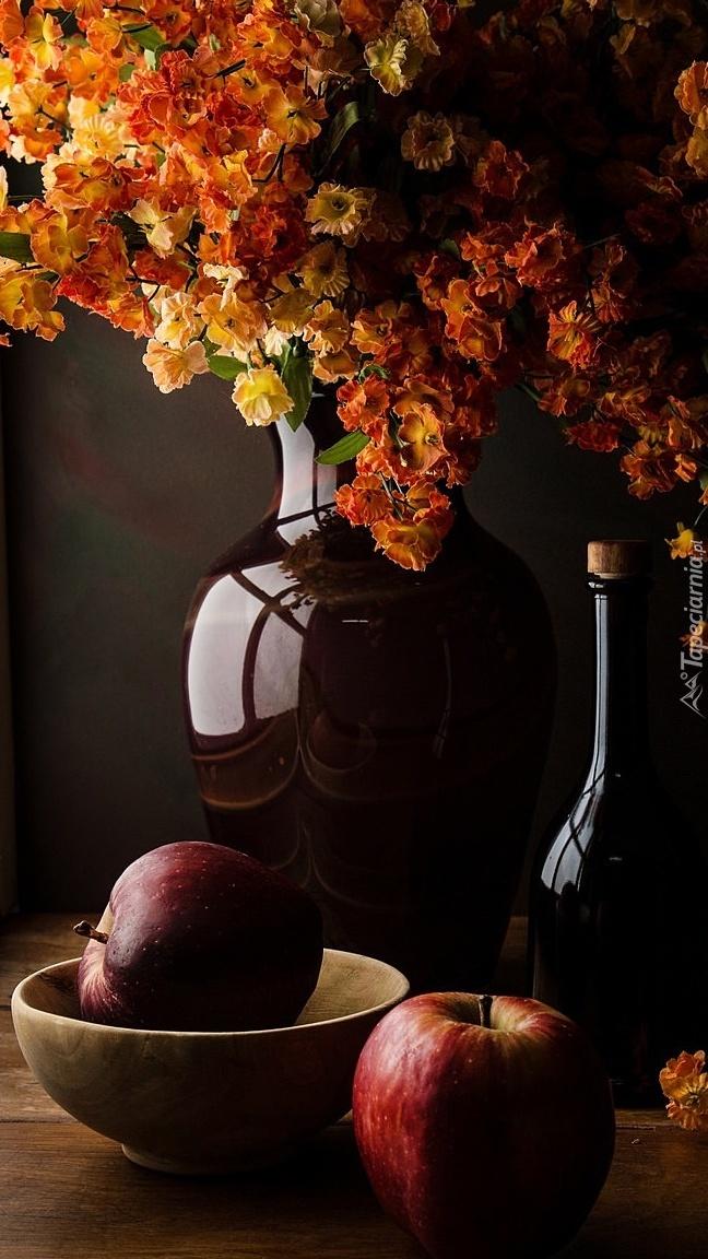 Jabłka obok wazonu z kwiatami