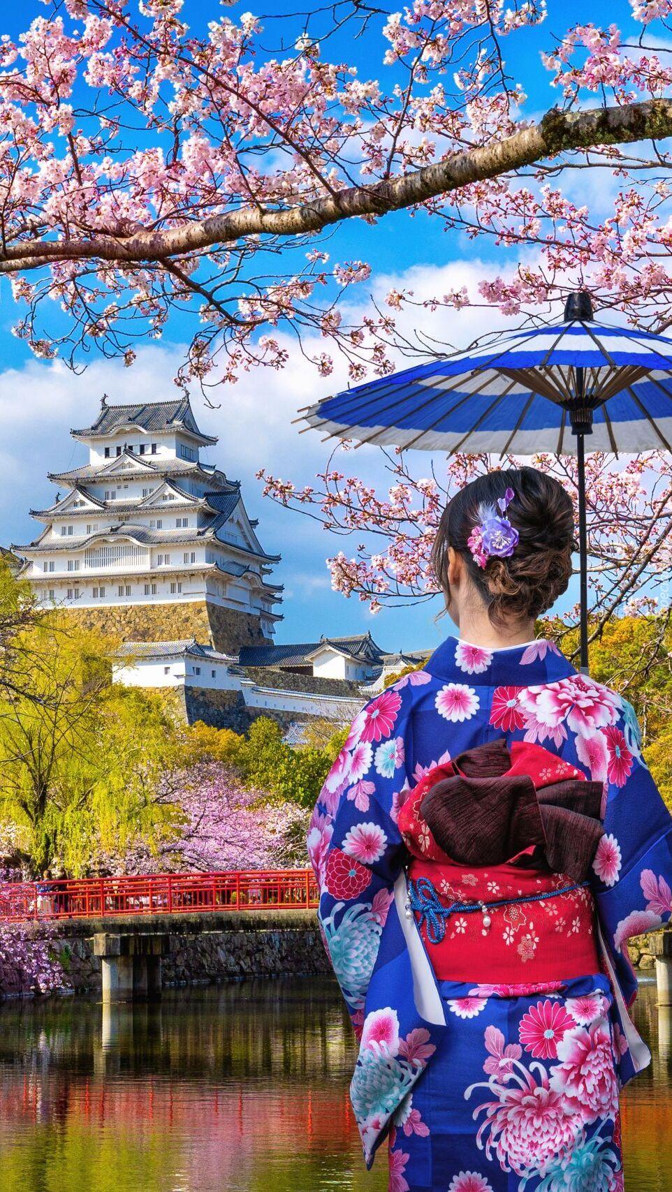 Japonka z parasolką na tle zamku Himeji