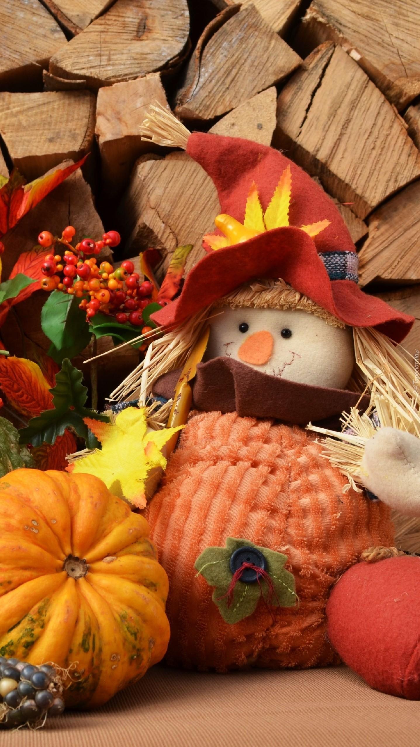 Jesienna laleczka przy stosie drewnna