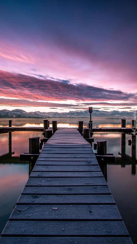 Jezioro z pomostem o zachodzie słońca