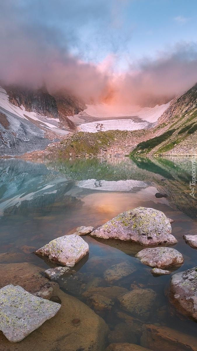 Kamienie w jeziorze u podnóża zamglonych gór